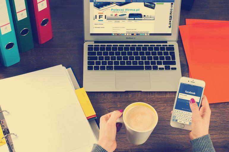 počítač, ženská ruka s mobilem v ruce kde je FB